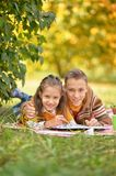 Brother and sister drawing. Brother and sister lying on green grass in autumnal park and drawing Stock Photo