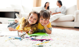 Brother and sister drawing lying on the floor Stock Images