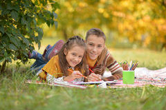 Brother and sister drawing. Brother and sister lying on green grass in autumnal park and drawing Stock Image