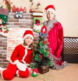 Brother and sister dressed costume Santa Claus by fireplace. Christmas Royalty Free Stock Photography