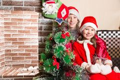 Brother and sister dressed costume Santa Claus by fireplace. Christmas Stock Images