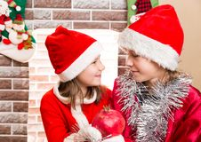 Brother and sister dressed costume Santa Claus by fireplace. Christmas Royalty Free Stock Image