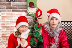 Brother and sister dressed costume Santa Claus by fireplace. Christmas Stock Photography