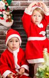 Brother and sister dressed costume Santa Claus by fireplace. Christmas Royalty Free Stock Photos