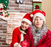 Brother and sister dressed costume Santa Claus by fireplace. Christmas Royalty Free Stock Photo