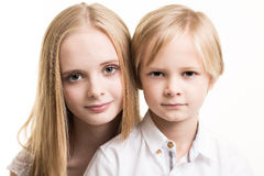 Brother And Sister Dressed In White In Studio. Stock Photography