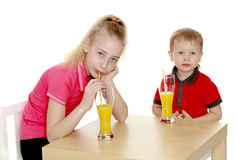 Brother sister drink juice sitting at the table Stock Image