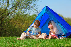 Brother and sister drinking water in tent outdoor Stock Photo