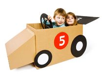 Brother and sister driving a cardboard car. Photo of a brother and sister driving their homemade cardboard car over white background stock photography