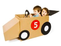 Brother and sister driving a cardboard car. Photo of a brother and sister driving their homemade cardboard car over white background stock photos