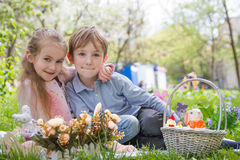 Brother and sister with easter decor. On green grass stock images