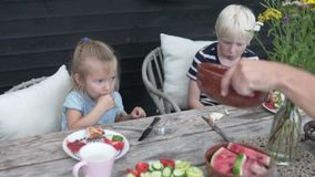 Brother and sister eat on the street in the country. Summer lunch on the veranda of a boy and a girl stock video