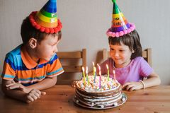 Brother and sister eating a birthday cake with candles blowing out and hugging. Children`s holiday and congratulations gifts. A family royalty free stock image