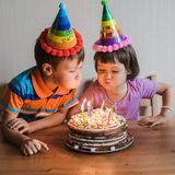 Brother and sister eating a birthday cake with candles blowing out and hugging. Children`s holiday and congratulations gifts. A family stock photo