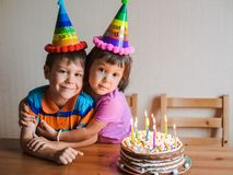 Brother and sister are eating a birthday cake and hugging. Children`s holiday and congratulations gifts. A family stock photo