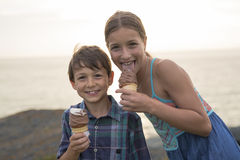 Brother and sister eating a delicious ice cream on the sunset. Stock Photo