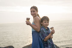 Brother and sister eating a delicious ice cream on the sunset. Stock Photos