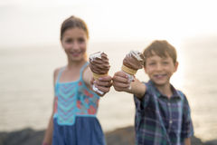 Brother and sister eating a delicious ice cream on the sunset. Stock Image