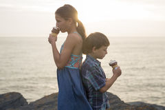 Brother and sister eating a delicious ice cream on the sunset. Stock Images