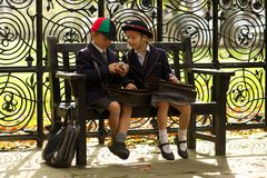 Brother and sister eating on wooden bench Royalty Free Stock Image