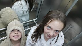 Brother and sister in elevator. Cute little brother and sister with bath robes going to swimming pool in spa center by the elevator Royalty Free Stock Images