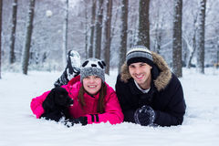 Brother and sister enjoying with his dog in the snow Stock Image