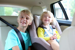 Brother and sister enjoying trip in the car. Happy kids, adorable toddler girl with teenager brother sitting together in modern car locked with safety belts Royalty Free Stock Photo