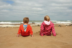 Brother and sister enjoying the view. Young brother and sister sitting on a sandy beach looking out to sea Stock Photos