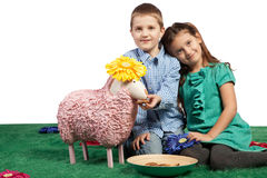 Brother and sister feeding a sheep. Cute young brother and sister cuddling up together with their woolly pink toy sheep and a plate of biscuits to feed it stock photography
