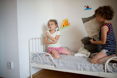 Brother and sister fight pillows on the bed in the bedroom. Stock Image
