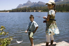 Brother and sister (7-10) fishing in lake, boy holding fish in net, girl holding rod, smiling, portrait Royalty Free Stock Photography