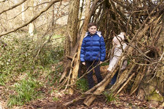 Brother and sister in a forest shelter made of tree branches Stock Image