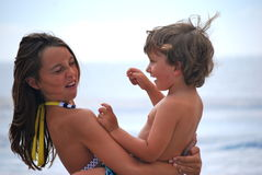 Brother and sister fun. A sister holding her brother or girl and boy having fun on the beach and showing expressions on their faces of fun and love and nose Stock Photos