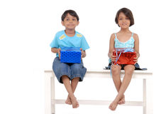 Brother and sister with gifts. Brother and sister sitting isolated to each other on bench holding surprise presents stock images