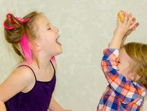 Children play together, laugh and fool around, have fun. A brother and sister, a girl and a boy, are playing with a donut and feeding each other at a party stock photos