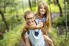 Brother and sister giving piggyback in forest royalty free stock photography