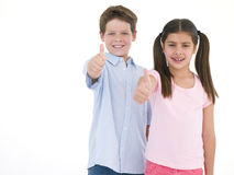 Brother and sister giving thumbs up smiling Stock Photos