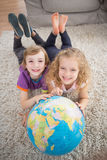 Brother and sister with globe lying on rug Stock Photos