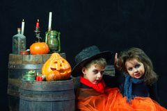 Brother and sister on Halloween. Funny kids in carnival costumes on dark background . Funny kids and pumpkins stock photography
