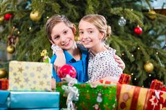 Brother and sister during handing out of presents, wishing Merry. Christmas Stock Image