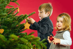 Brother and sister hanging Christmas tree decorations Royalty Free Stock Photography