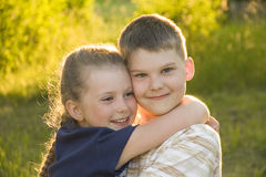 Brother and sister. Happy brother and sister embrace on a background of meadows illuminated by the evening sun Royalty Free Stock Photography