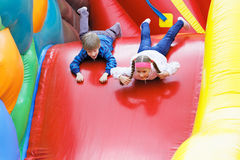 Brother and sister have fun in attraction. Brother and sister have fun in the park on an inflatable attraction royalty free stock photography
