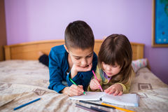 Brother and Sister Having Fun drawing at bed Stock Photography
