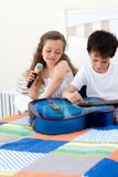 Brother and sister having fun with a guitar Stock Photography