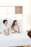 Brother and sister having fun in parent's bedroom Royalty Free Stock Image