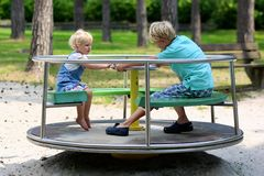 Brother and sister having fun at playground. Happy children, two siblings, smiling blonde toddler girl in casual outfit and teenager boy having fun riding merry Royalty Free Stock Photography