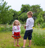 Brother and sister are playing. Brother and his sister playing in national costumes Royalty Free Stock Image