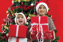 Brother and sister hold gifts in hand on Christmas evening Royalty Free Stock Photo