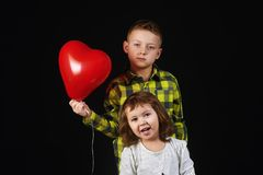 Brother and sister holding balloons stock image